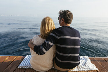 Mature couple sitting on jetty, relaxing at the sea - EBSF02647