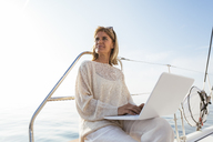 Woman sitting on catamaran, using laptop - EBSF02650