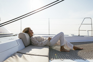 Mature woman relaxing on a sailing trip - EBSF02653