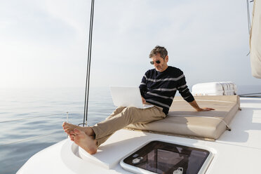 Mature man sitting on deck of a catamaran, using laptop - EBSF02656