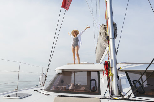 Mature woman standing on catamaran, waving with raised arms - EBSF02659