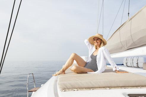 Mature woman relaxing on a catamaran, taking a sunbath - EBSF02662