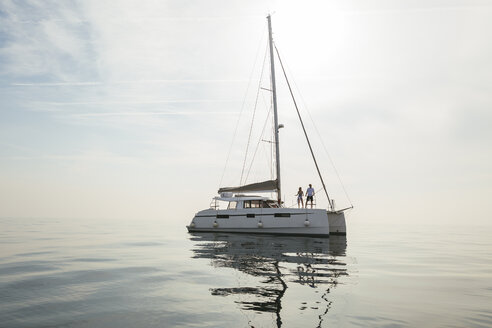 Couple setting off for a sailing trip on a catamaran - EBSF02665