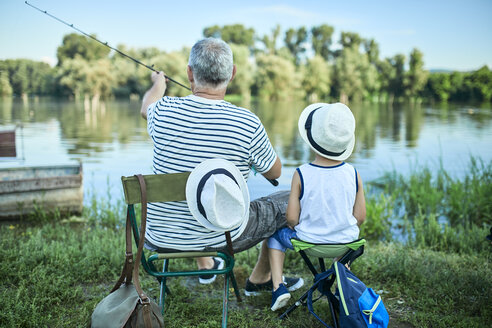 Back view of grandfather and grandson fishing at lakeshore - ZEDF01474