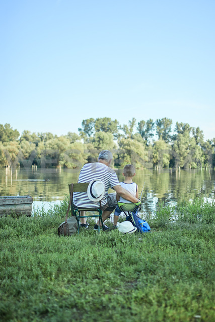 Back view of grandfather and grandson fishing together at lakeshore - ZEDF01480