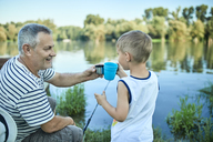 Grandfather and grandson toasting together at lakeshore - ZEDF01486