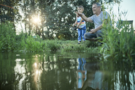 Grandfather and grandson fishing together at lakeshore - ZEDF01489