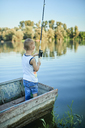 Back view of little boy with fishing rod standing in boat - ZEDF01492