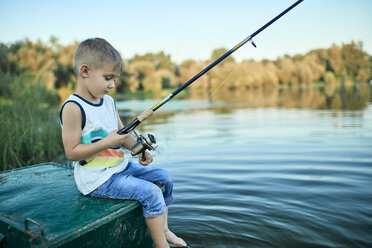 Back view of little boy with fishing rod sitting on boat - ZEDF01495