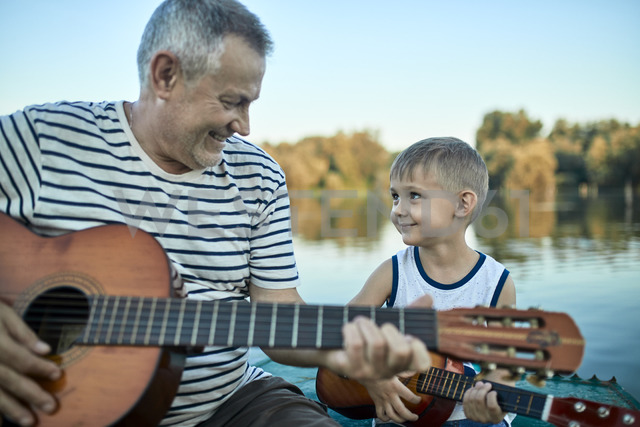 Grandfather teaching grandson playing guitar - ZEDF01498 - Zeljko Dangubic/Westend61
