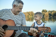 Grandfather teaching grandson playing guitar - ZEDF01498