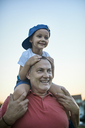 Portrait of happy little boy on shoulders of his grandfather - ZEDF01501