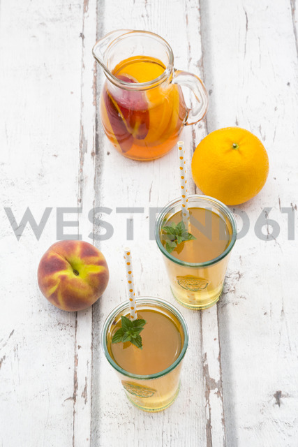 Glasses and jar of peach orange ice tea on wood - LVF07310