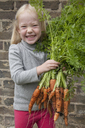 A young girl holding a large bunch of carrots. - MINF00276