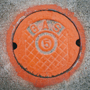 A gas manhole cover, round and painted orange on the road in Seattle. - MINF00339