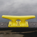 A large yellow mooring cleat on the wharf side in Seattle. - MINF00345