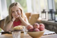 A young girl looking at a pastry pie, smiling. - MINF00396