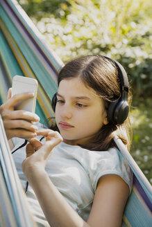 Portrait of girl with headphones and smartphone in hammock - LVF07321