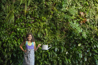 Outdoors in the city in spring. An urban lifestyle. A young girl standing in front of a wall covered with ferns and climbing plants. - MINF00448