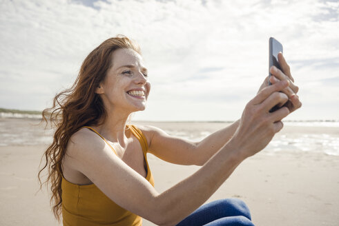 Netherlands, Zeeland, grinning redheaded woman taking selfie with smartphone on the beach - KNSF04194