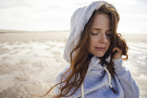 Netherlands, Zeeland, portrait of redheaded woman with freckles wearing hooded jacket on the beach - KNSF04197