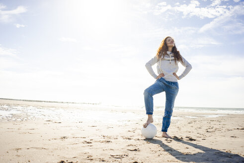 Netherlands, Zeeland, woman with football on the beach - KNSF04200