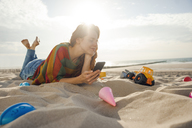 Netherlands, Zeeland, woman with smartphone relaxing on the beach - KNSF04203