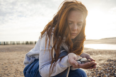 Netherlands, Zeeland, portrait of redheaded woman with collected seashells on the beach - KNSF04206