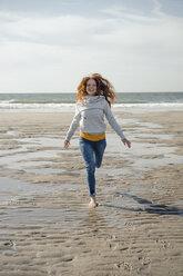 Netherlands, Zeeland, happy redheaded woman running on the beach - KNSF04209