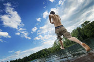 A boy taking a running jump into a calm pool of water, from a wooden jetty. - MINF00465