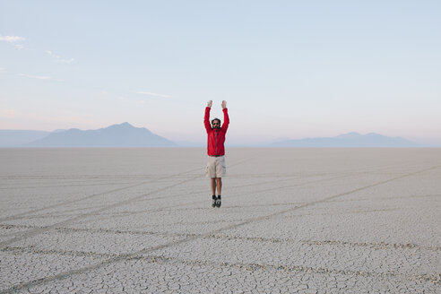 A man jumping in the air on the flat desert or playa or Black Rock Desert, Nevada. - MINF00501