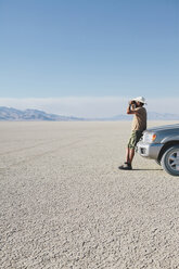 A man leaning against a truck, looking through binoculars. - MINF00504