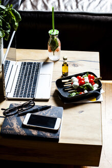 Lunch with Caprese salad and bottle of infused water at home office - SBDF03671