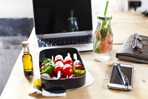 Lunch box of Caprese salad, bottle of infused water and laptop on desk - SBDF03674