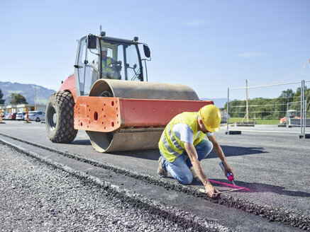 Worker marking roadside on construction site - CVF00982