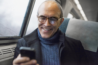A mature man sitting by a window in a train carriage, using his mobile phone, keeping in touch on the move. - MINF00551
