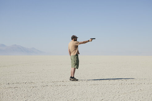 Man aiming hand gun, standing in vast, barren desert - MINF00724