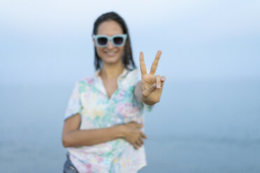 Smiling woman showing victory sign, close-up - AFVF00871
