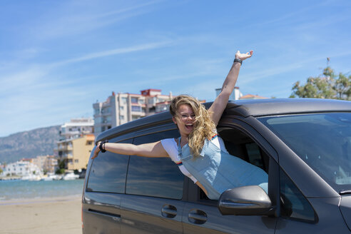 Happy woman leaning out of car window on a road trip - AFVF00872