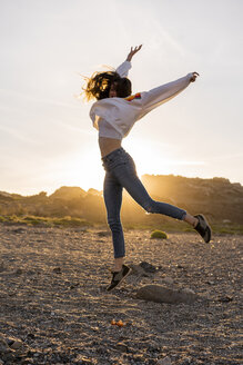 Young woman at the beach, dancing at sunset - AFVF00887