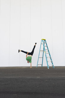 Acrobat training one-armed handstand next to ladder - AFVF00892