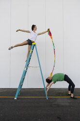 Two acrobats exercising trick on a ladder with a ribbon - AFVF00901