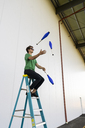 Acrobat wearing sunglasses, sitting on ladder, juggling - AFVF00910