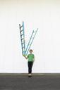 Acrobat balancing ladder upside down in his hand - AFVF00934