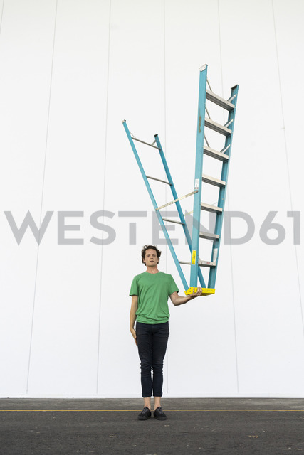 Acrobat balancing ladder upside down in his hand - AFVF00937