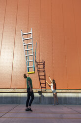 Acrobat balncing ladder on his face while colleague is trying to catch its shadow - AFVF00946