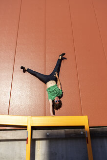 Acrobat performing one-armed handstand on yellow frame - AFVF00949