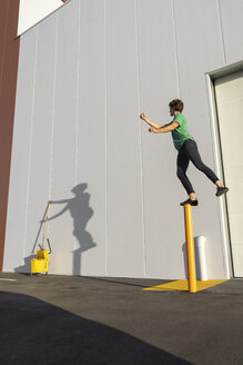 Acrobat standing on pole, casting shadow at cleaning bucket - AFVF00976