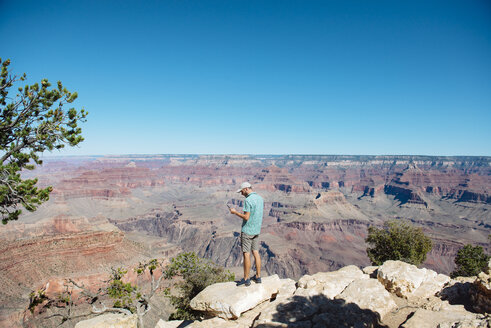 USA, Arizona, Grand Canyon National Park, Grand Canyon, man looking at smartphone - GEMF02166