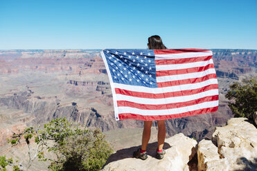 USA, Arizona, back view of woman with American flag enjoying view of Grand Canyon National Park - GEMF02172